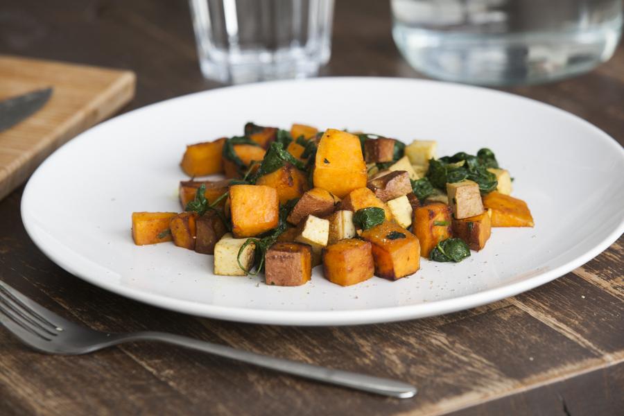 Batata doce e espinafre com curry e tofu em prato branco sobre mesa de madeira e garfo ao lado
