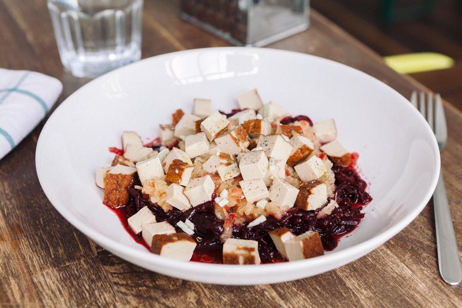 Beterraba ralada e salada de maçã com tofu defumado em prato branco sobre mesa de madeira com talher e copo