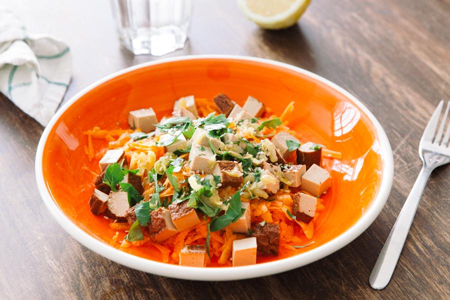 Prato com cenoura e tofu com molho de semente de gergelim sobre mesa de madeira