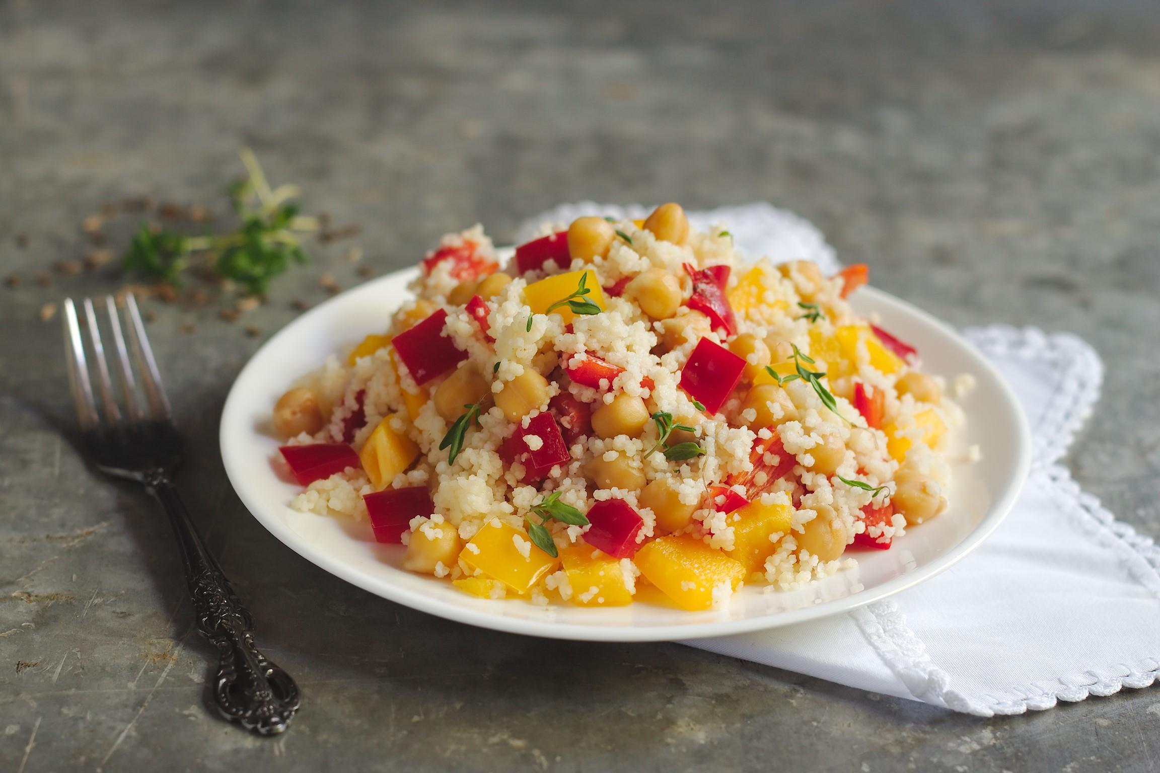 Prato branco com cuscuz com grão de bico e vegetais sobre guardanapo de tecido ao lado de um garfo