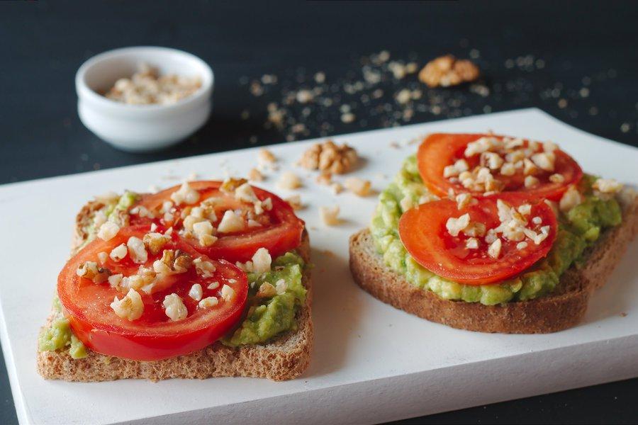 Abacate e tomate no pão integral com amendoins sobre louça branca com pote ao fundo