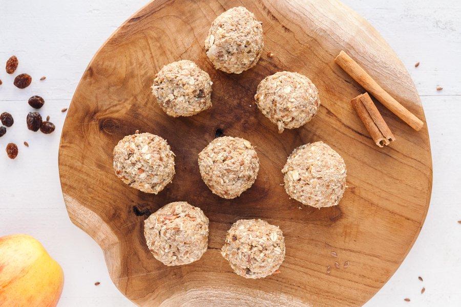 Aperitivos de maçã e pasta de amendoim sobre madeira circular com decoração de canela e frutos ao redor