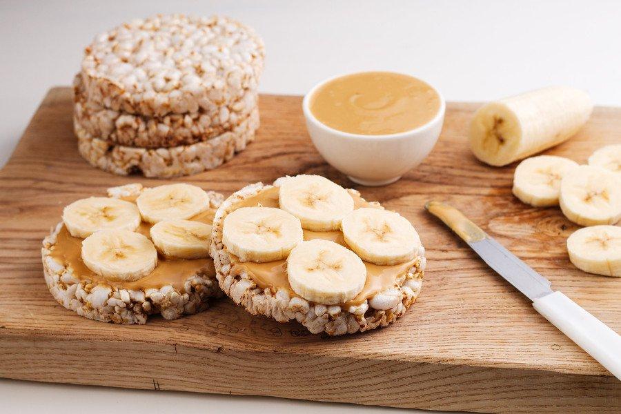 Banana e manteiga de amendoim com biscoitos de arroz distribuídos sobre tábua de madeira