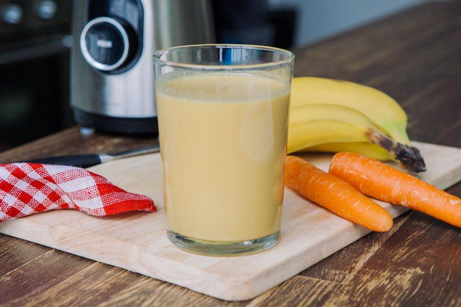 Copo de smoothie de café da manhã sobre tábua em mesa de madeira. Ao lado se vê bananas, cenouras, um guardanapo e parte de um liquidificador