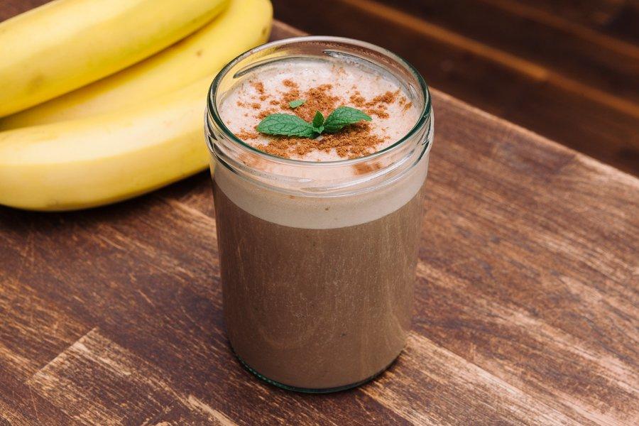Smoothie de café e hortelã em copo de vidro sobre mesa de madeira e um cacho de bananas ao fundo